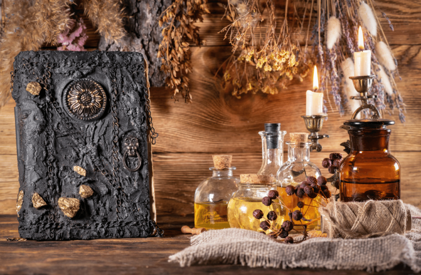 IMAGE: another stunning altar that celebrates the elements: comeplete with an array of oils in bottles, dried flowers hung upside down, a candle that is nearly burned out and a handmade, black book of shadows with a faded golden sunflower at it's center. This altar is gently composed in front of a wall made of wood planks.